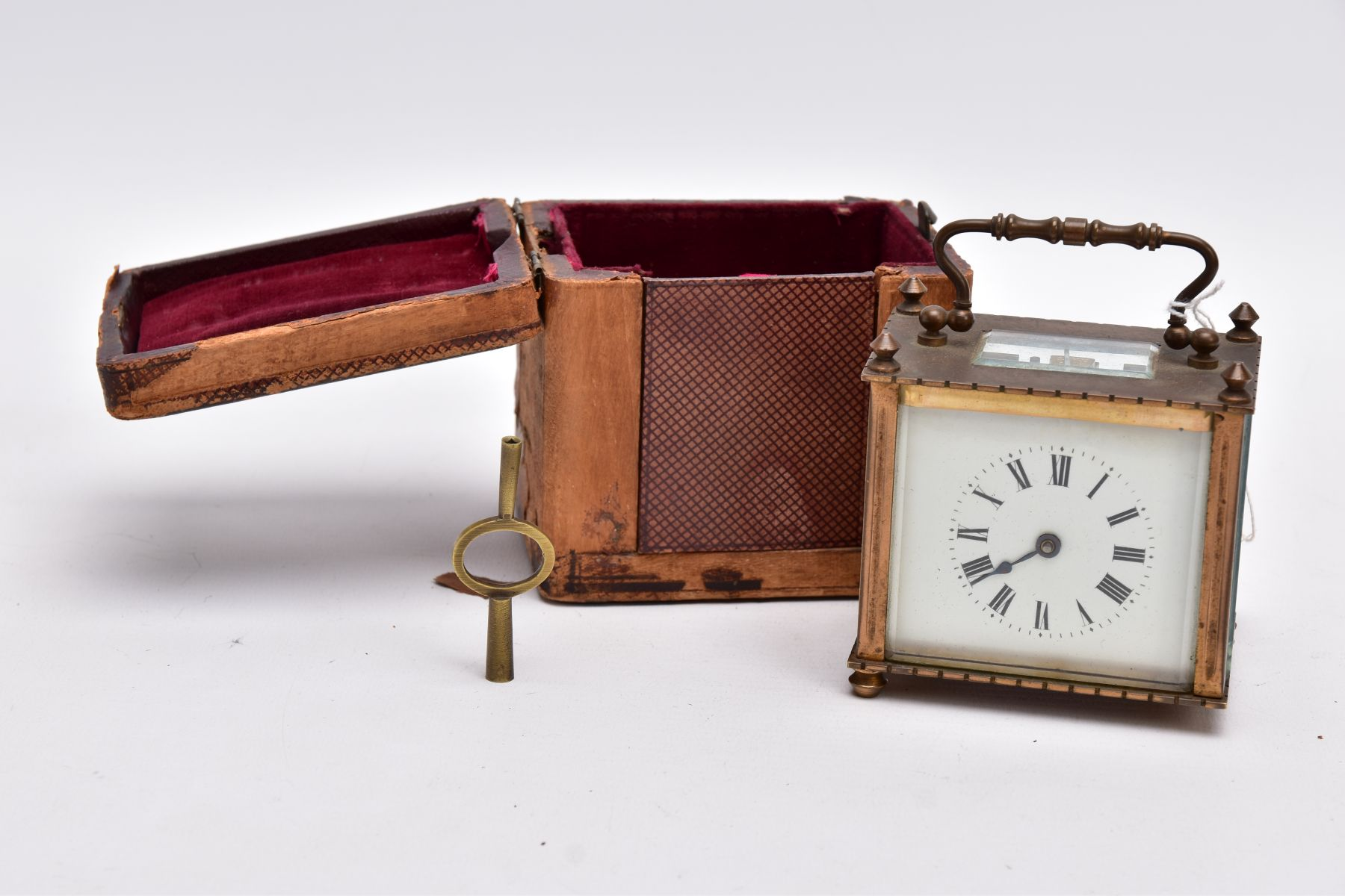 A SMALL LEATHER CASED BRASS TRAVEL CARRIAGE CLOCK, glass panels, white dial with roman numerals,
