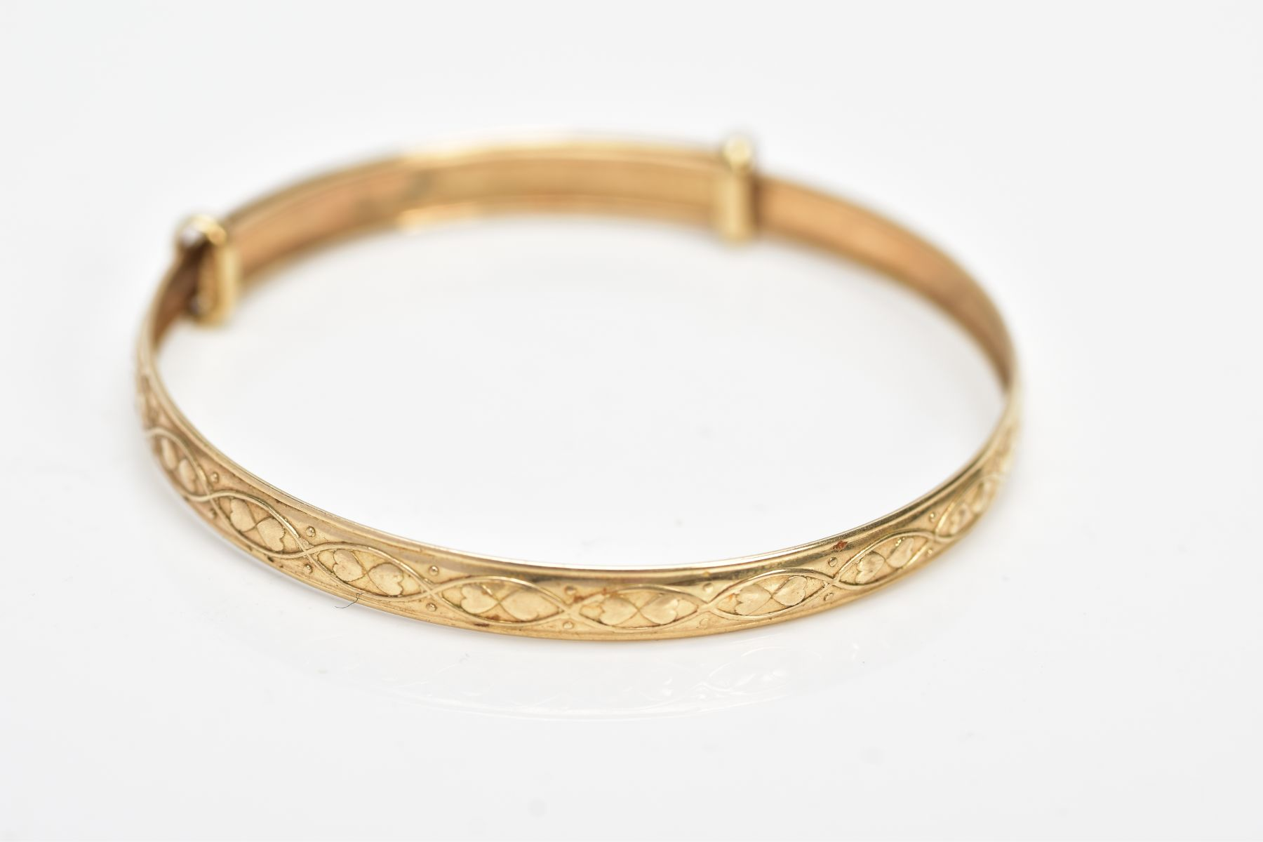A 9CT GOLD CHRISTENING BANGLE, embossed heart and scroll design, hallmarked 9ct gold Birmingham,