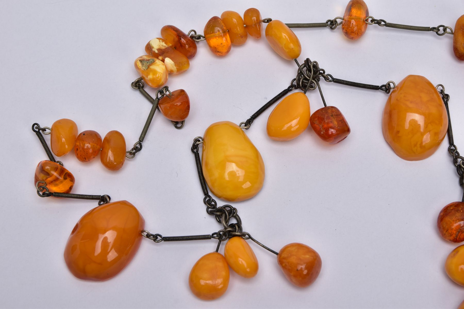 AN AMBER NECKLACE, designed with a mixture of transparent and butterscotch coloured amber in various - Image 3 of 4