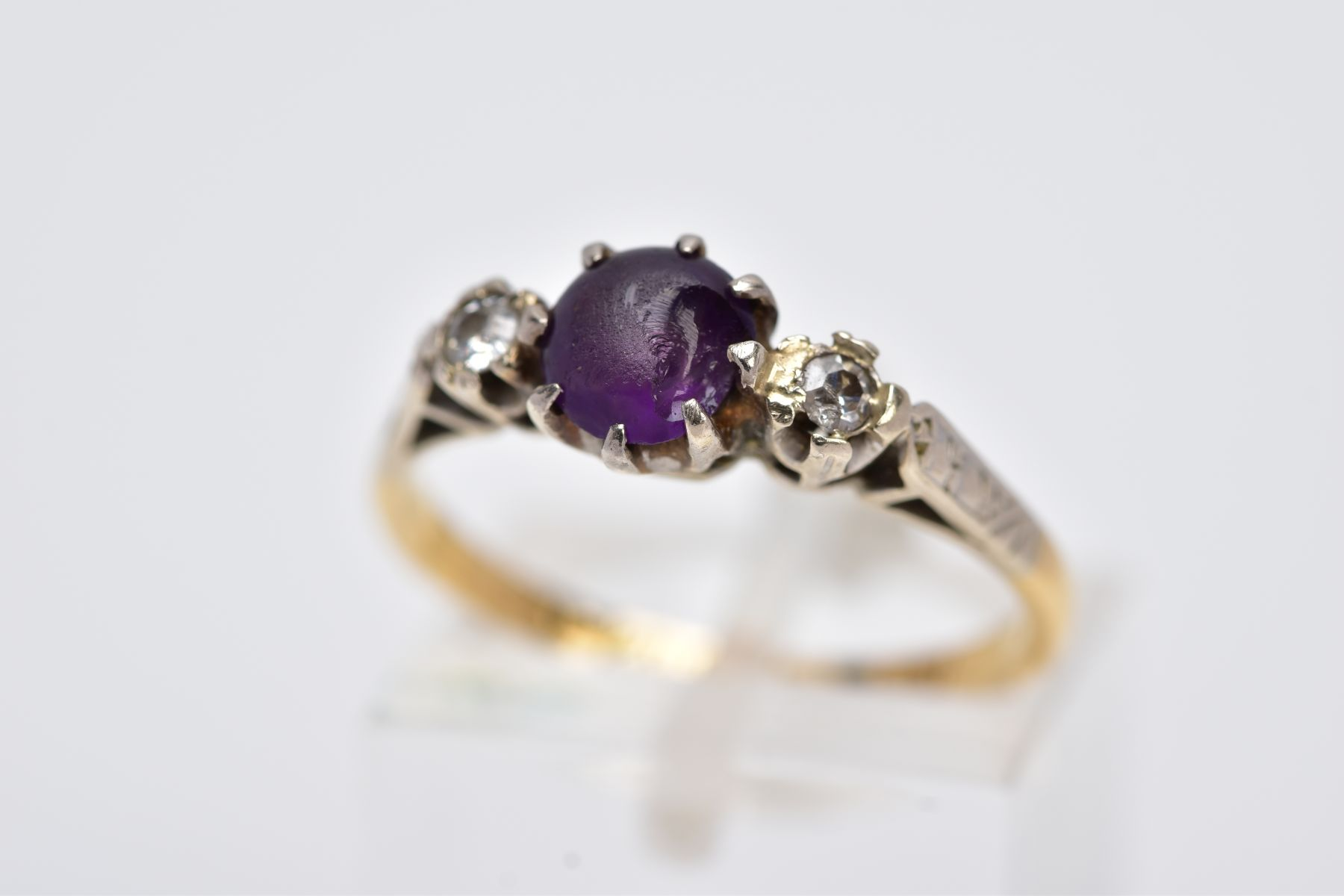 A YELLOW METAL THREE STONE RING, design with a central circular cut purple stone, assessed as paste,