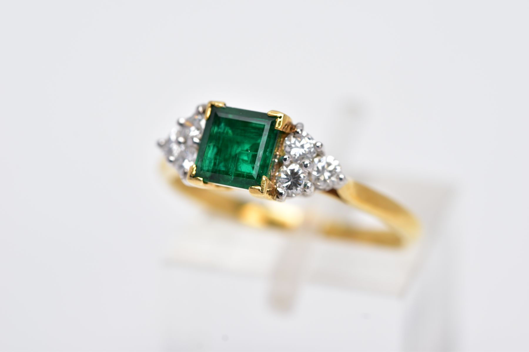 A LATE 20TH CENTURY 18CT GOLD EMERALD AND DIAMOND RING, centring on a square cut emerald measuring