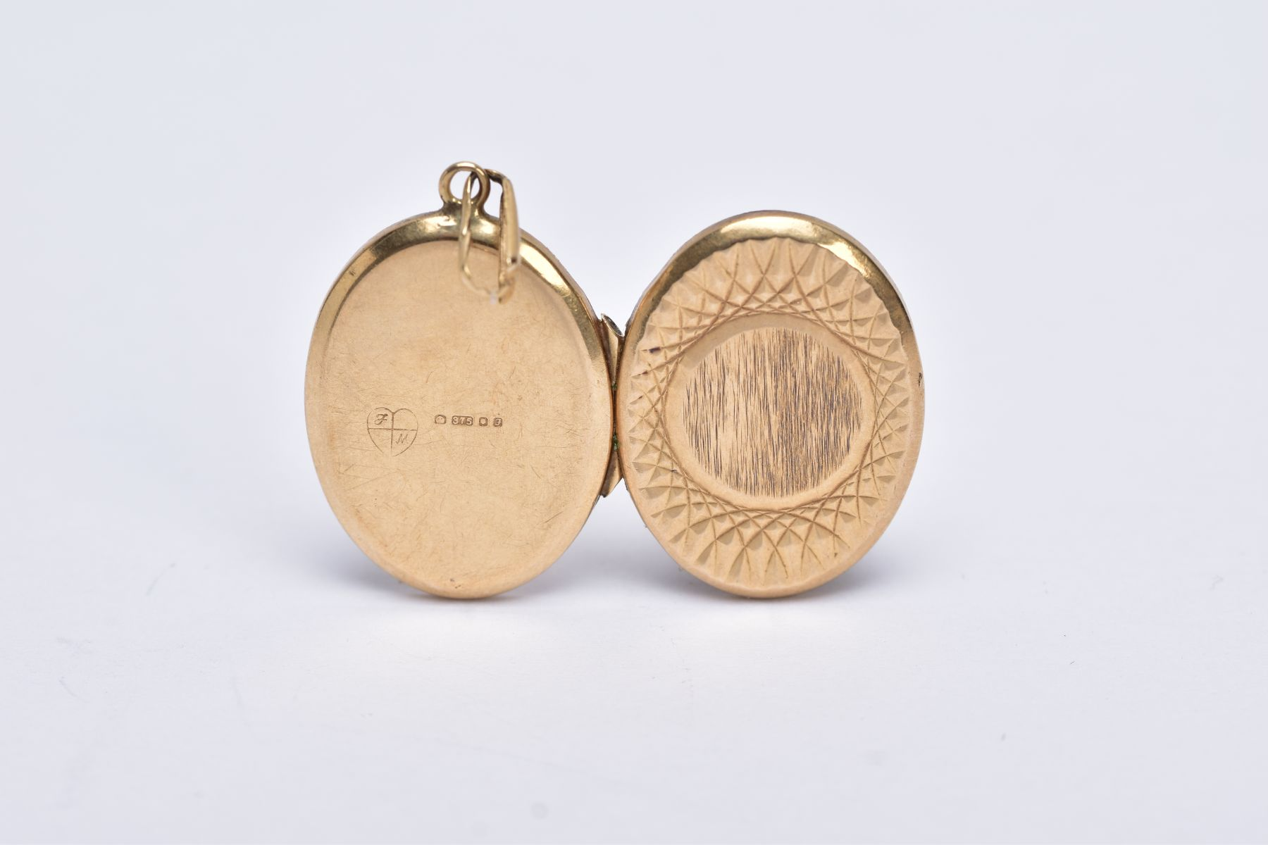 A 9CT GOLD OVAL LOCKET PENDANT, textured design with a vacant cartouche, fitted with a tapered