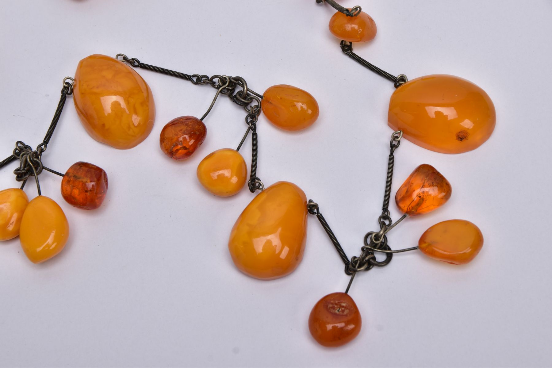 AN AMBER NECKLACE, designed with a mixture of transparent and butterscotch coloured amber in various - Image 2 of 4