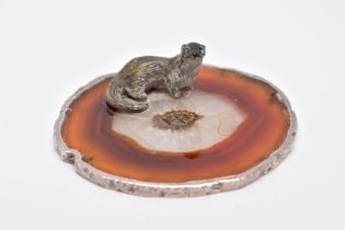 A WHITE METAL OTTER ON AN AGATE AND SILVER MOUNTED BASE, textured figure of an otter fixed onto a
