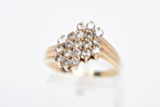 A YELLOW METAL DIAMOND CLUSTER RING, an asymmetrical cluster design with claw set, round brilliant