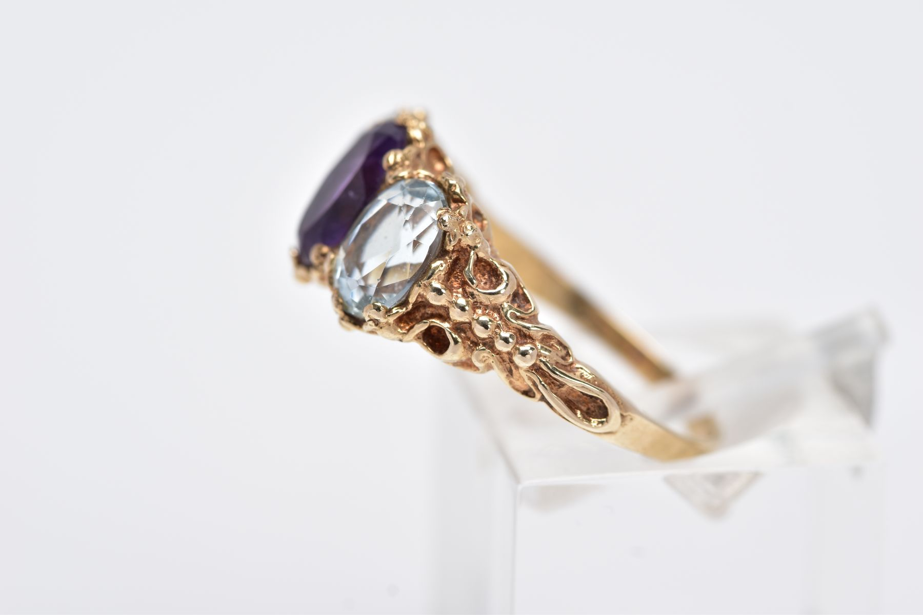 A 9CT GOLD THREE STONE RING, centring on an oval cut amethyst, flanked with two oval cut - Image 2 of 4