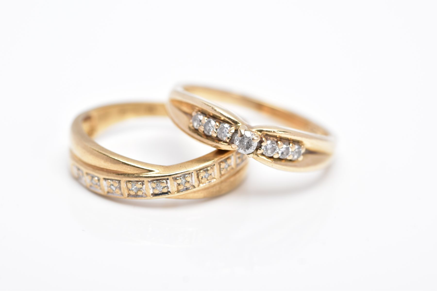 TWO 9CT GOLD DIAMOND RINGS, the first designed with a row of seven round brilliant cut diamonds,