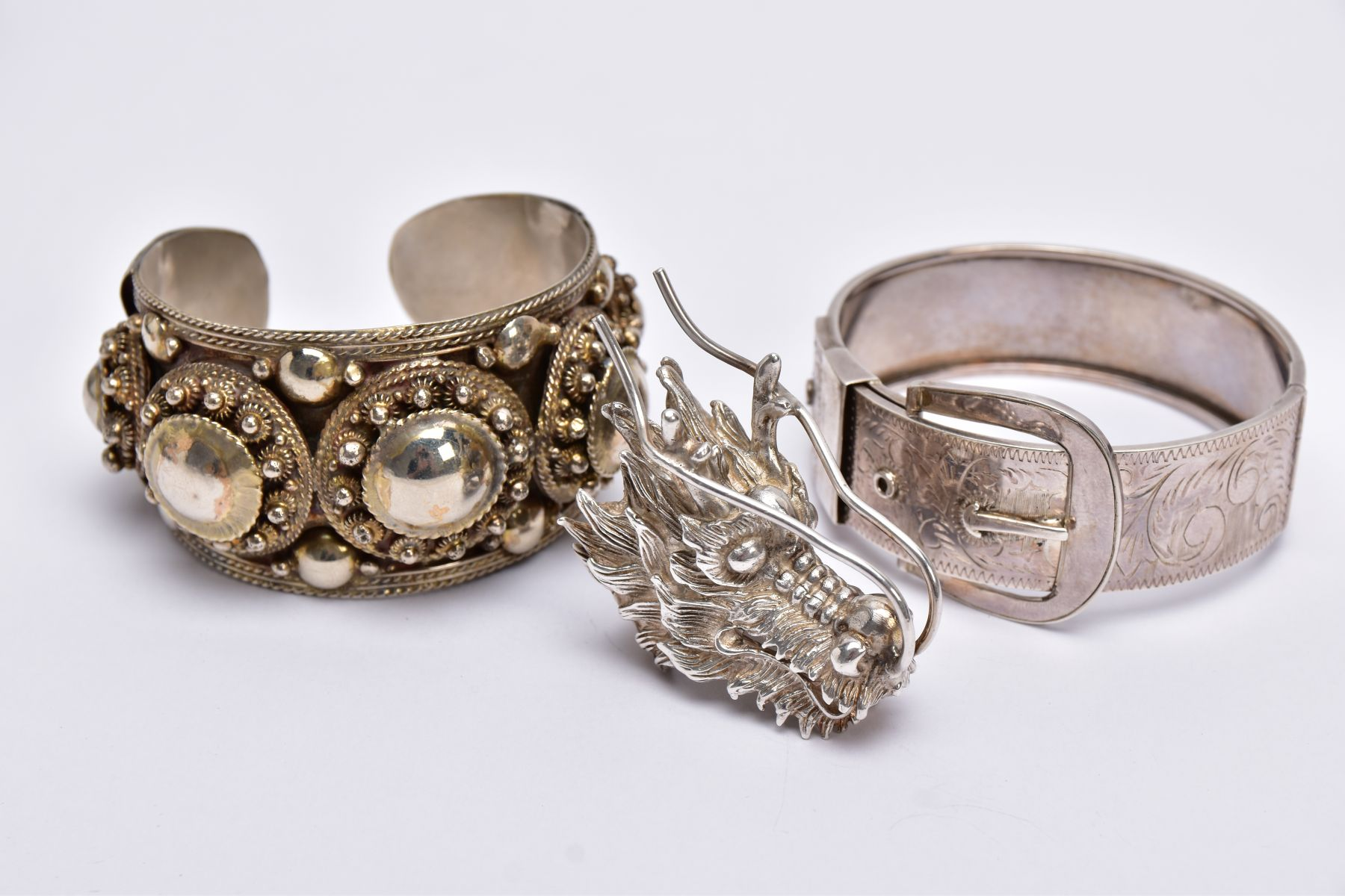 A WHITE METAL BANGLE, CUFF BANGLE AND A RING, the hinged bangle of a belt and buckle design, foliate - Image 2 of 5
