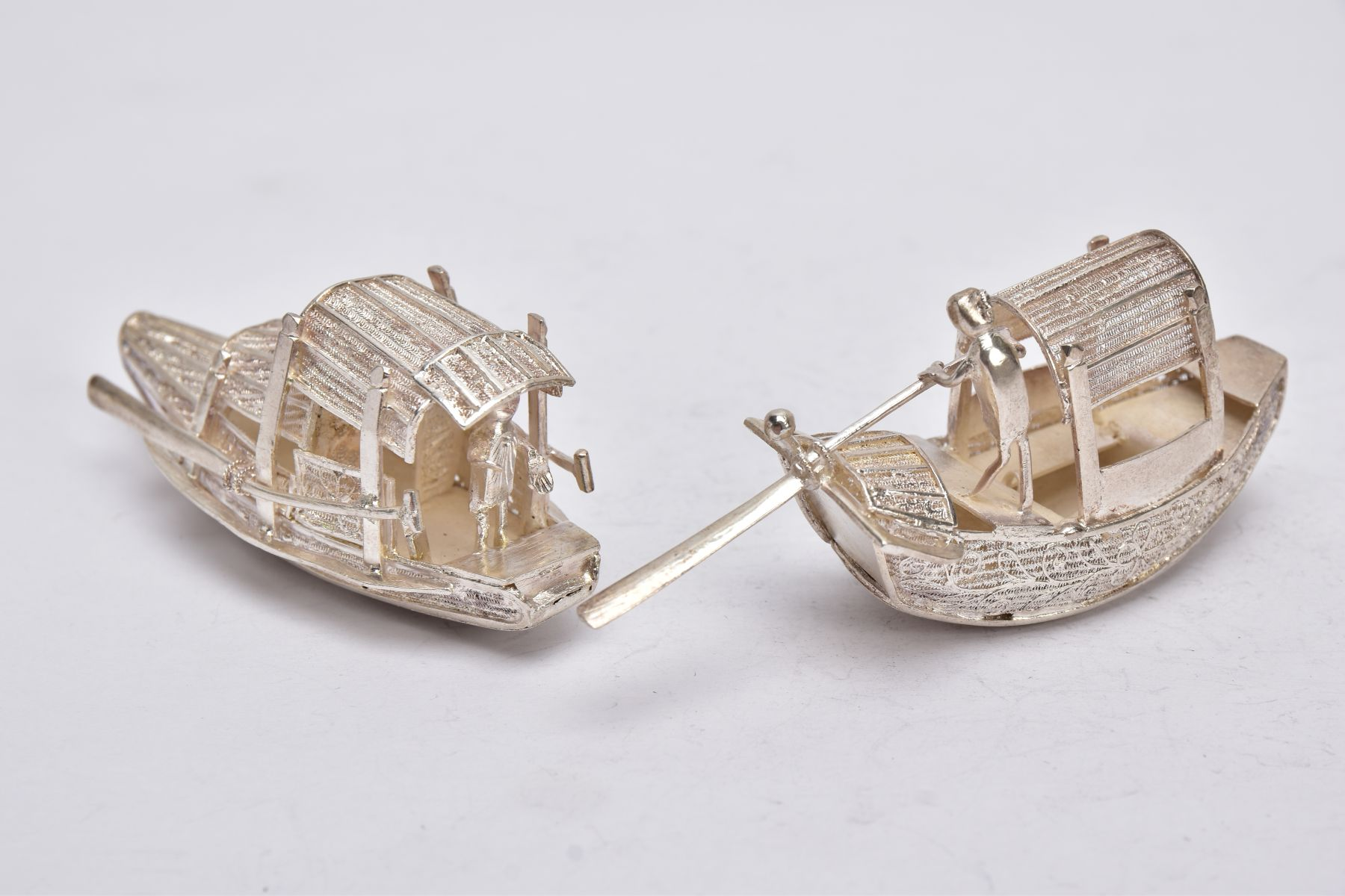 TWO MODERN ORIENTAL, WHITE METAL FILIGREE BOAT ORNAMENTS, one with a standing figure with paddle,
