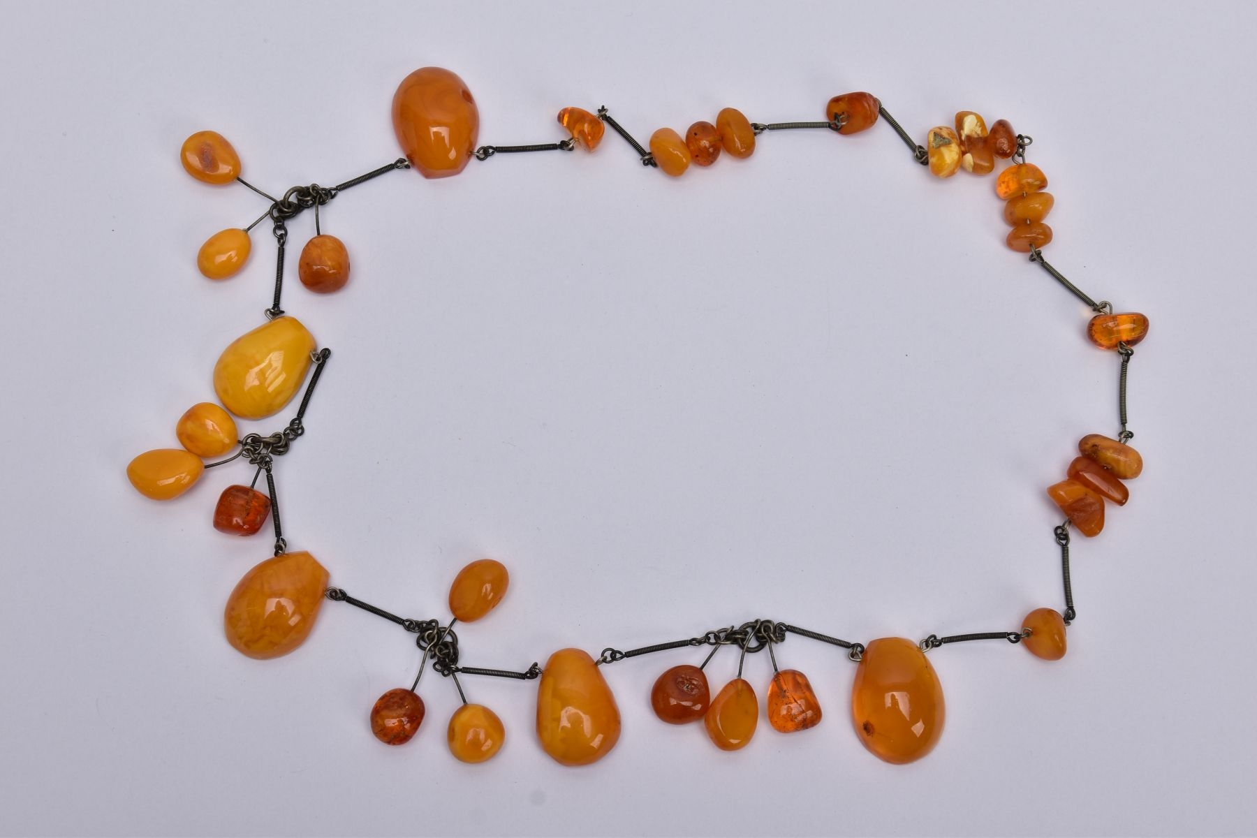 AN AMBER NECKLACE, designed with a mixture of transparent and butterscotch coloured amber in various