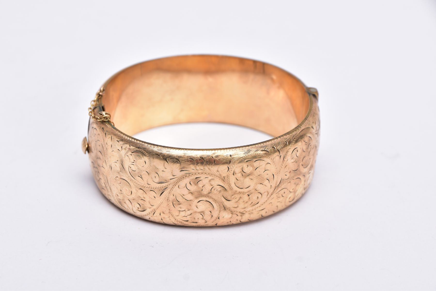 A ROLLED GOLD WIDE BANGLE, hinged bangle with a half engraved foliate design, push pin clasp, fitted