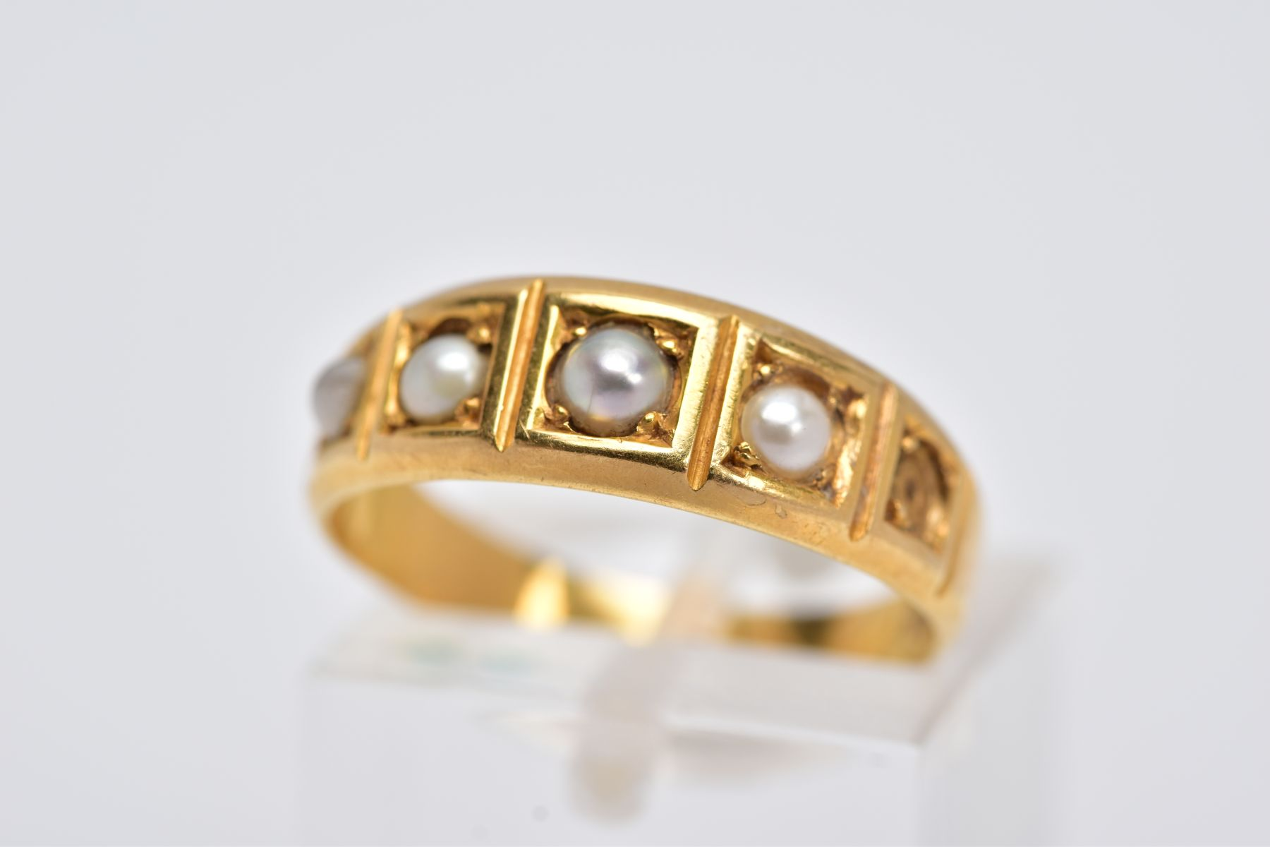 A YELLOW METAL CULTURED PEARL RING, designed with a five square section, three set with cultured