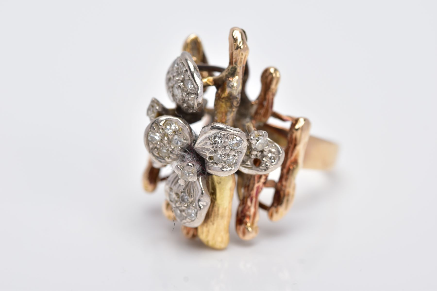 A YELLOW METAL DIAMOND SET RING, of a floral and bark textured design in the style of Andrew