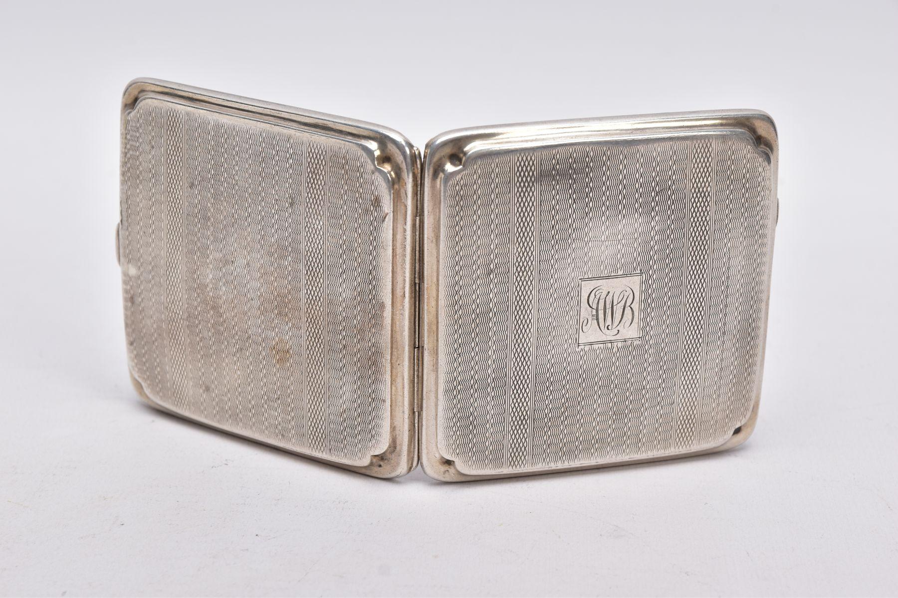 A SILVER CIGARETTE CASE, of an engine turn design, engraved monogram, missing elastic straps on