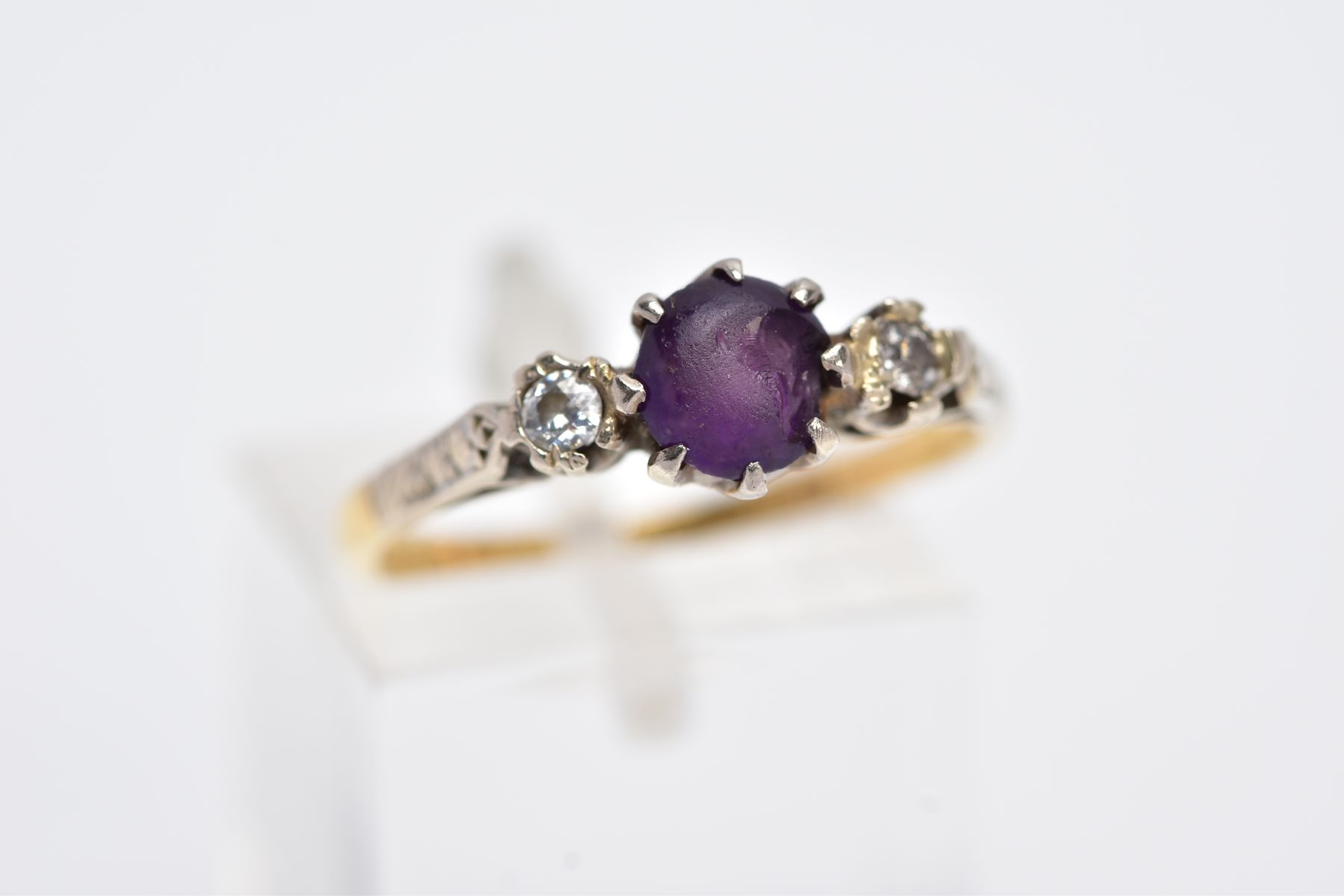A YELLOW METAL THREE STONE RING, design with a central circular cut purple stone, assessed as paste, - Image 4 of 4