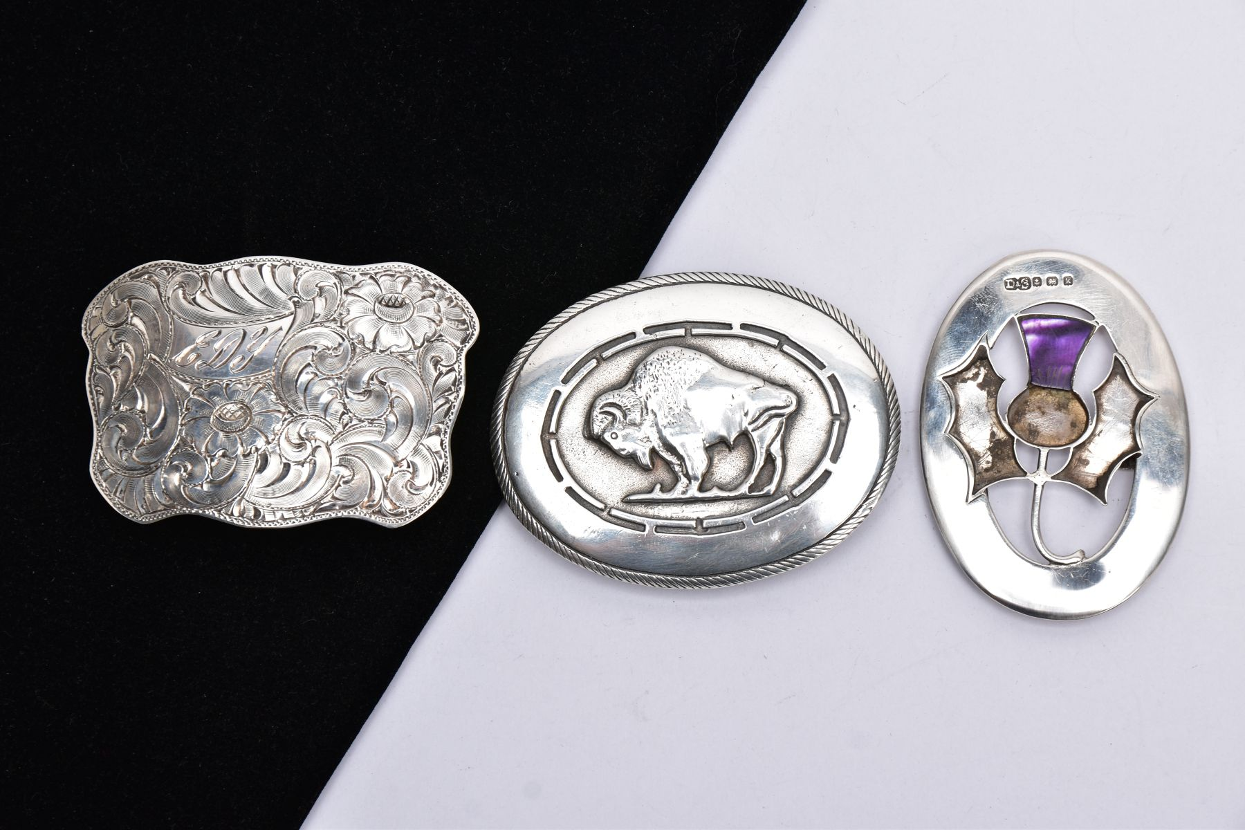 THREE BELT BUCKLES, to include an AF silver oval buckle depicting a thistle, with missing mother