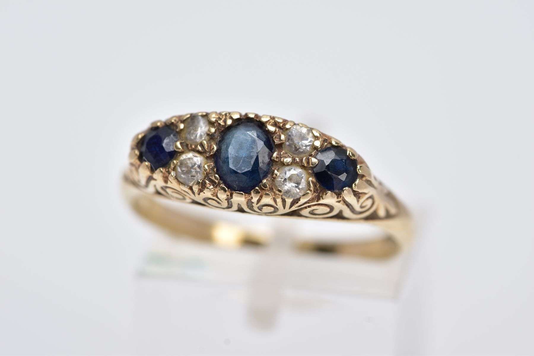 A 9CT GOLD SAPPPHIRE AND PASTE RING, centring on an oval cut blue sapphire flanked with colourless