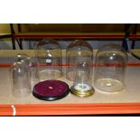 SEVEN VARIOUS GLASS/PLASTIC DOMES AND STANDS, comprising three with wooden bases, height 28cm, three