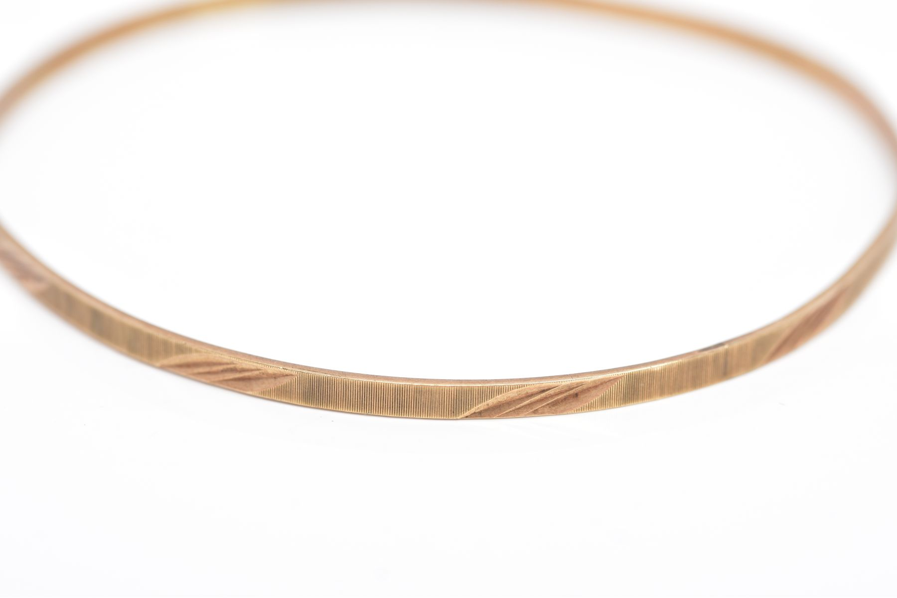 A 9CT GOLD BANGLE, thin bangle with a textured and foliate engraved design, hallmarked 9ct gold - Image 2 of 3