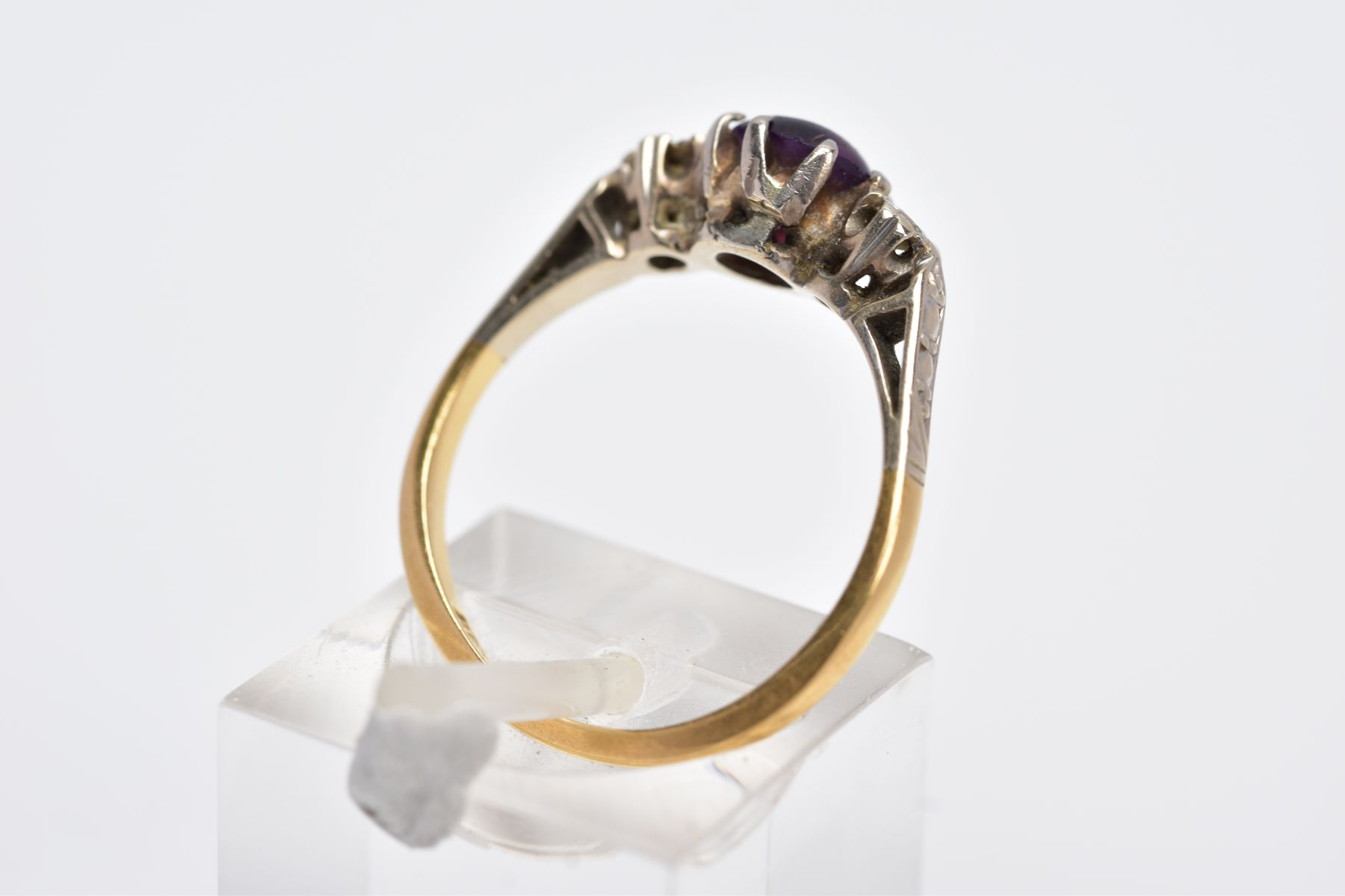 A YELLOW METAL THREE STONE RING, design with a central circular cut purple stone, assessed as paste, - Image 3 of 4