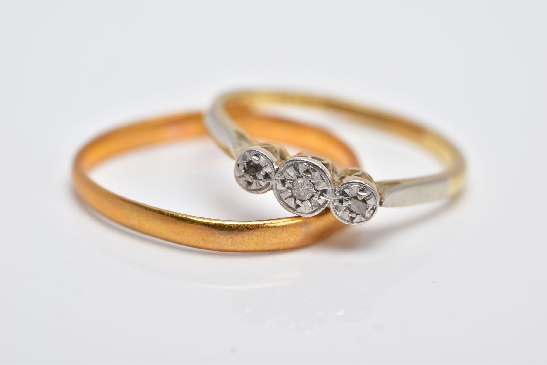 A YELLLOW METAL THREE STONE DIAMOND RING AND A 22CT GOLD BAND, the diamond ring centring on an