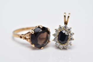A 9CT GOLD SMOKEY QUARTZ RING AND A 9CT GOLD SAPPHIRE PENDANT, the ring designed with a claw set,