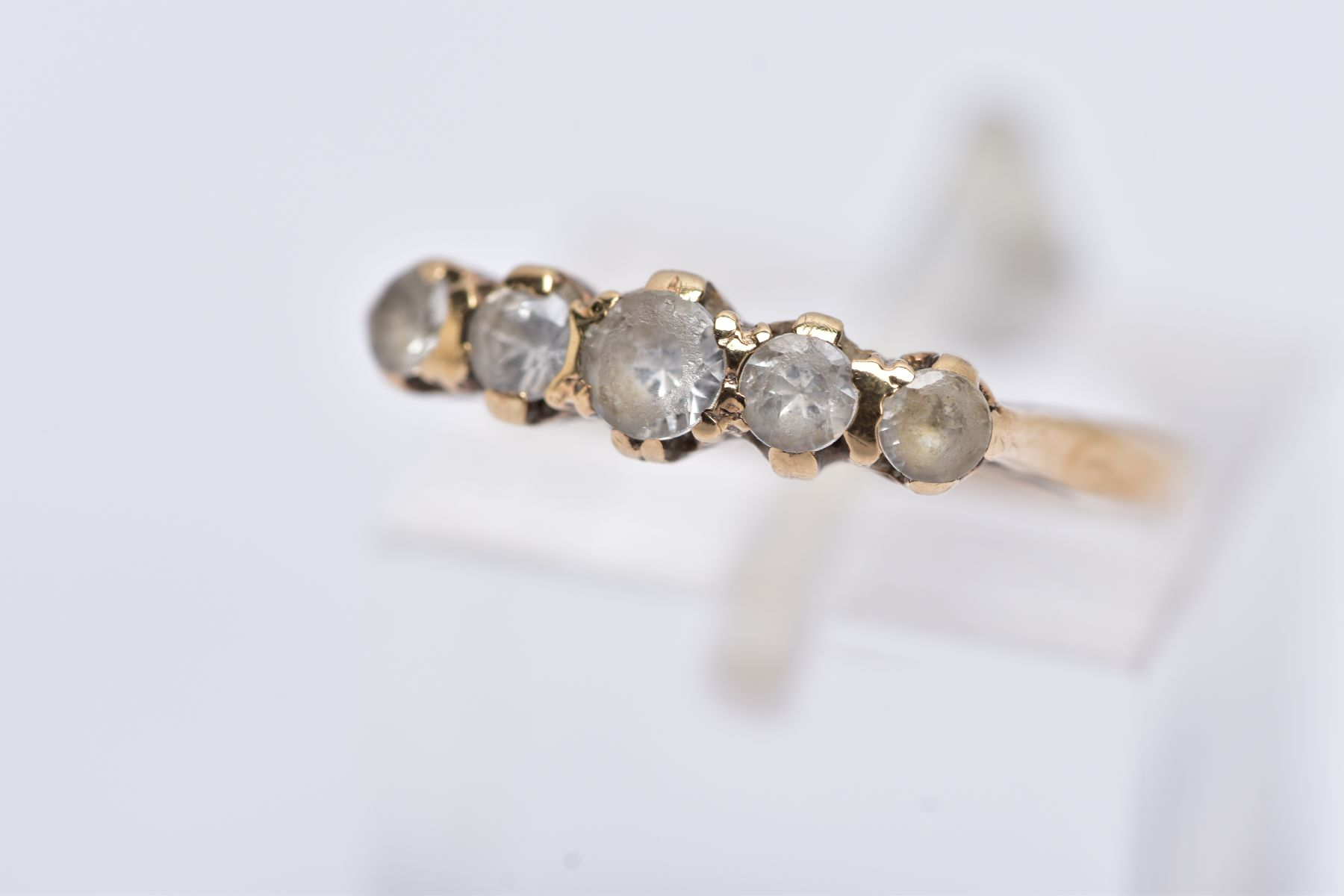 A YELLOW METAL FIVE STONE RING, designed with a row of graduate circular cut colourless spinel's