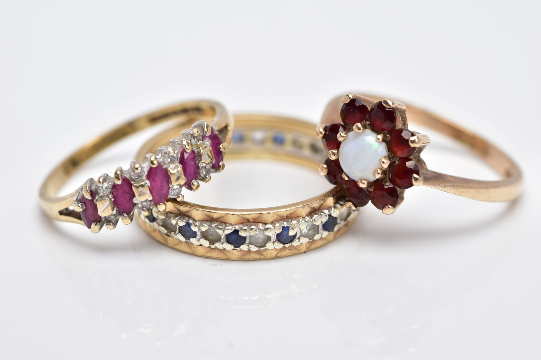 THREE 9CT GOLD GEM SET RINGS, to include a full eternity ring set with colourless spinel and blue
