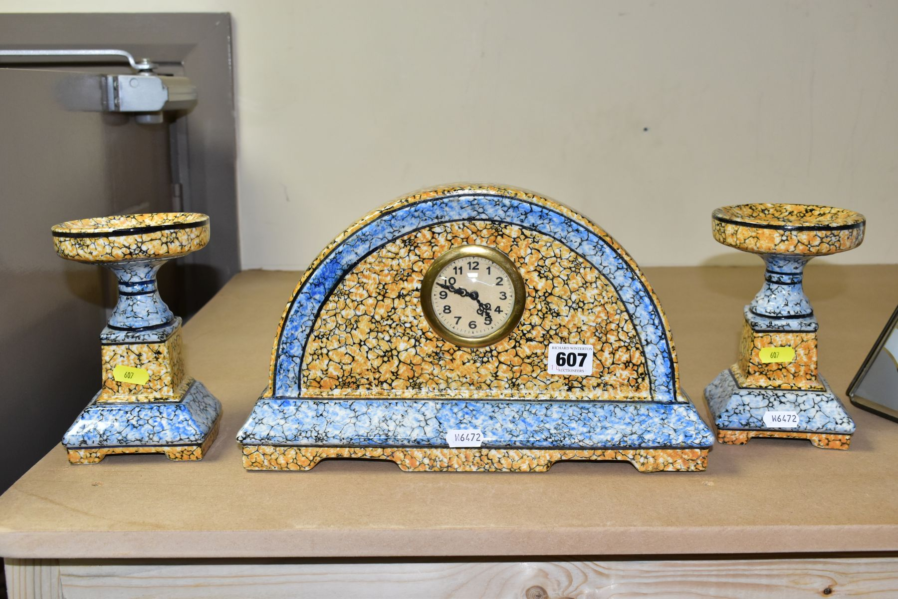 A CONTINENTAL CLOCK GARNITURE, the dome shaped porcelain clock is branded M.W inside a triangle,