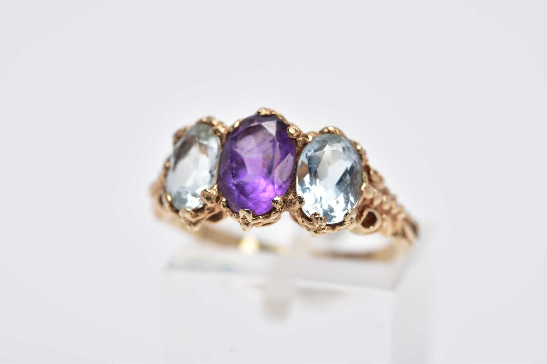 A 9CT GOLD THREE STONE RING, centring on an oval cut amethyst, flanked with two oval cut
