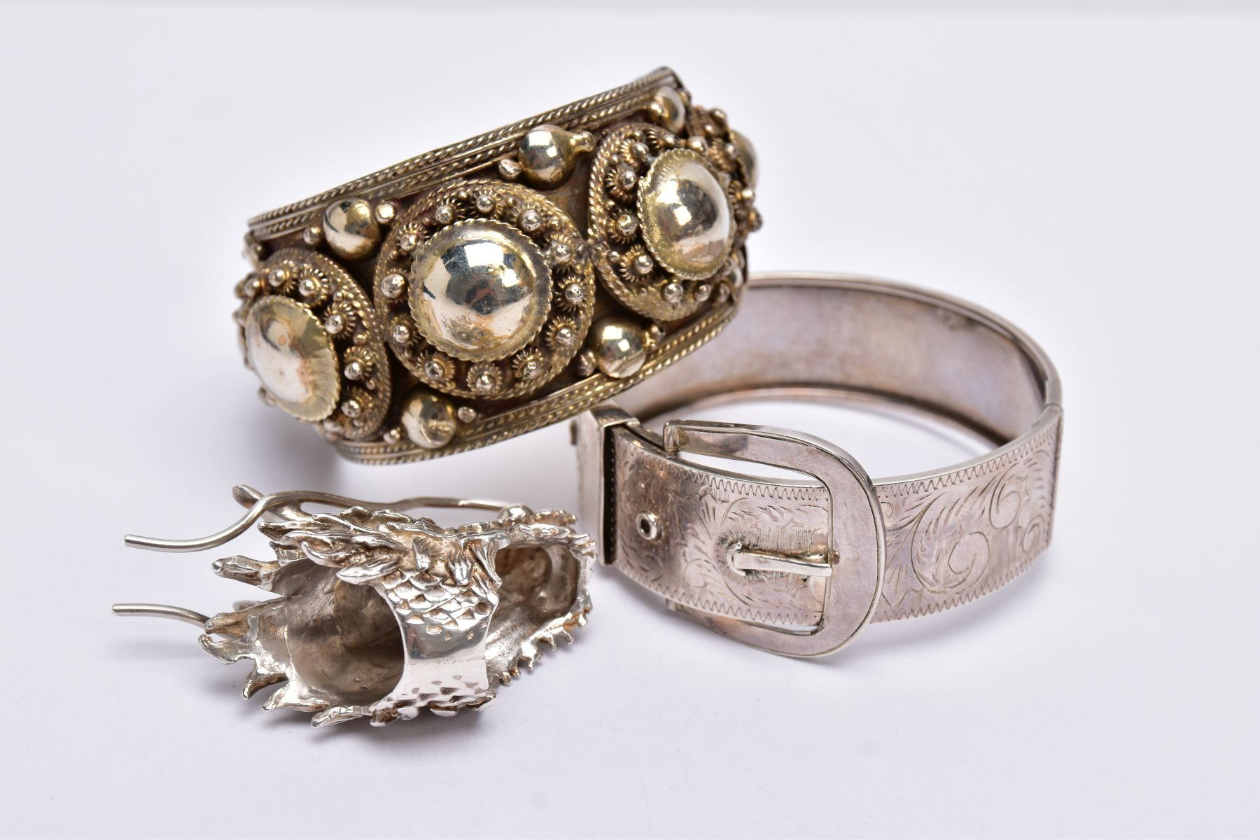 A WHITE METAL BANGLE, CUFF BANGLE AND A RING, the hinged bangle of a belt and buckle design, foliate - Image 4 of 5
