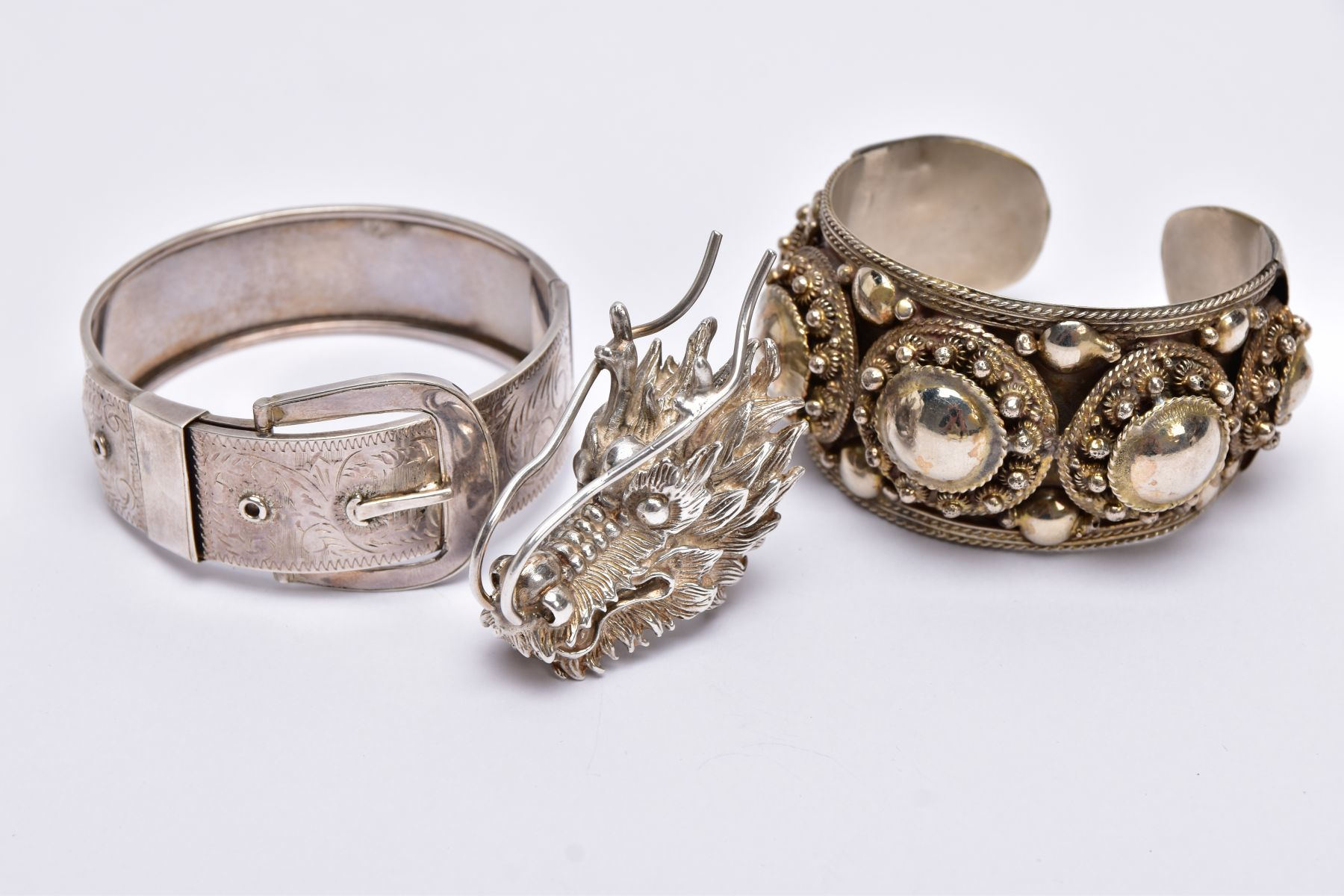 A WHITE METAL BANGLE, CUFF BANGLE AND A RING, the hinged bangle of a belt and buckle design, foliate