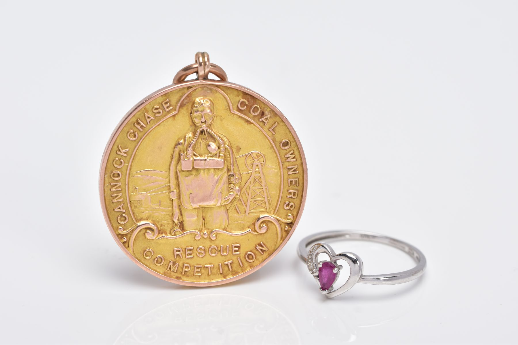 A 9CT GOLD MOUNTED MEDAL AND A 9CT WHITE GOLD RUBY AND DIAMOND RING, the medal of a circular form,