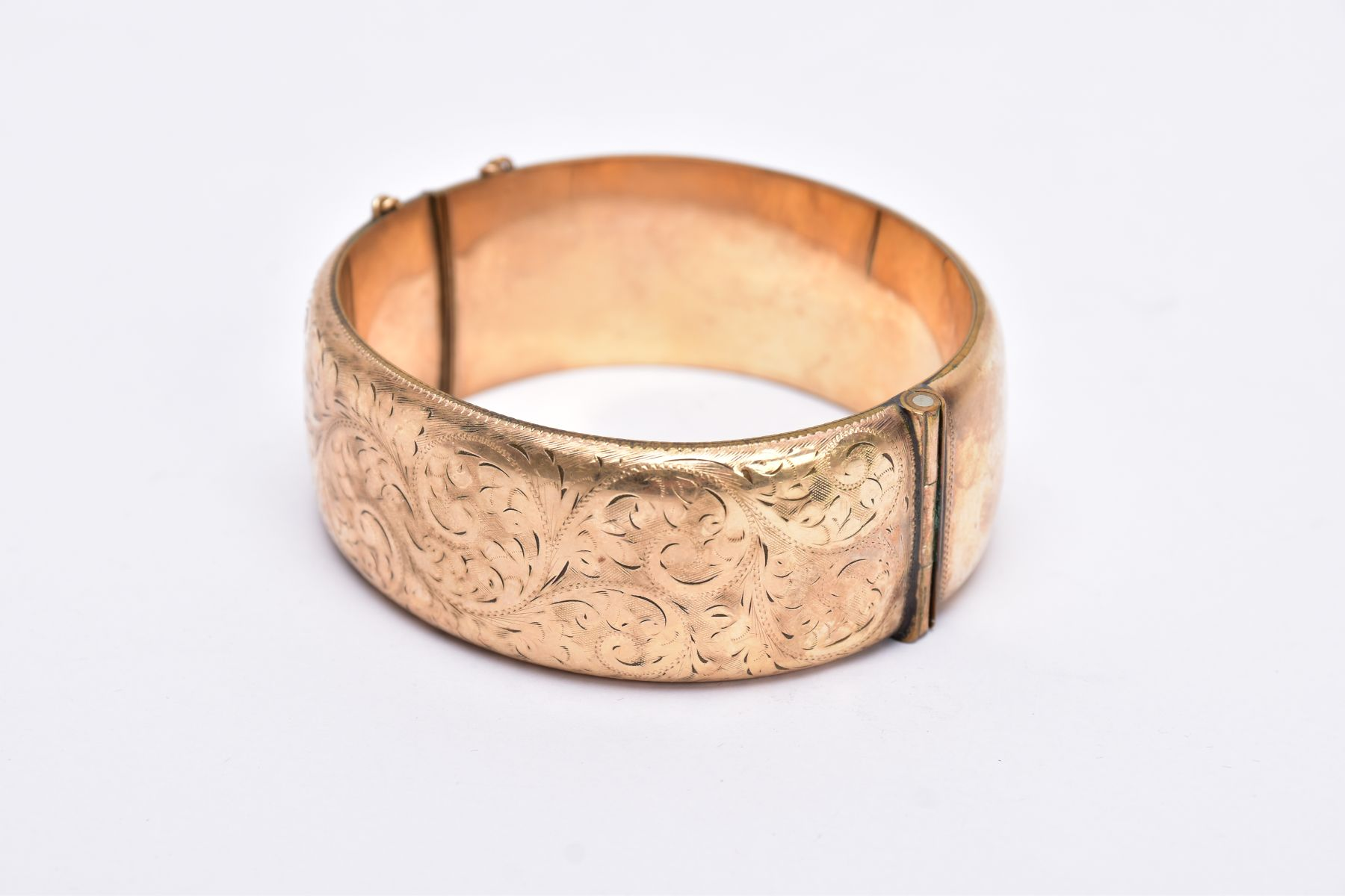 A ROLLED GOLD WIDE BANGLE, hinged bangle with a half engraved foliate design, push pin clasp, fitted - Image 2 of 3