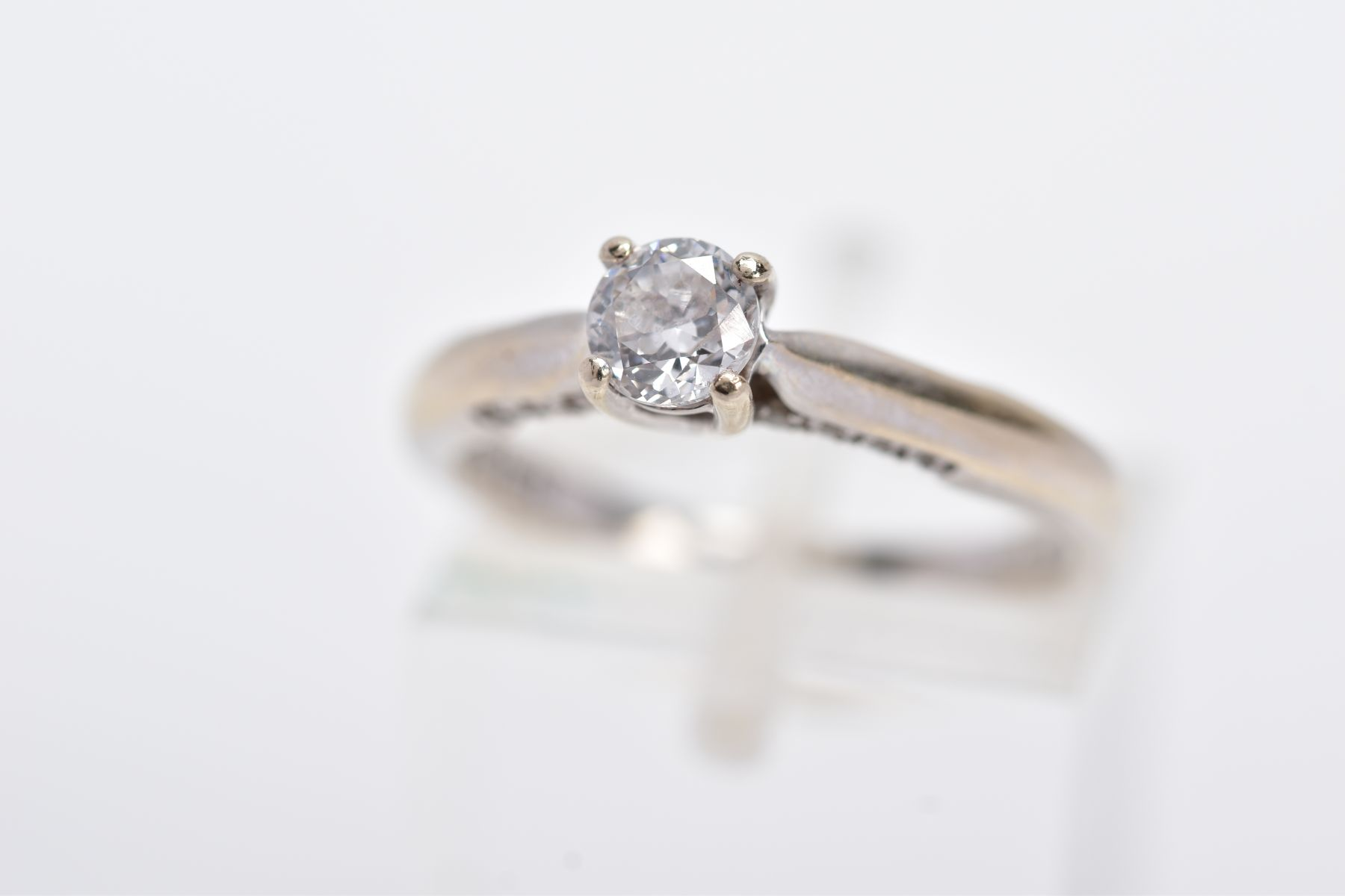 AN 18CT WHITE GOLD DIAMOND RING, designed with a central claw set, round brilliant cut diamond,