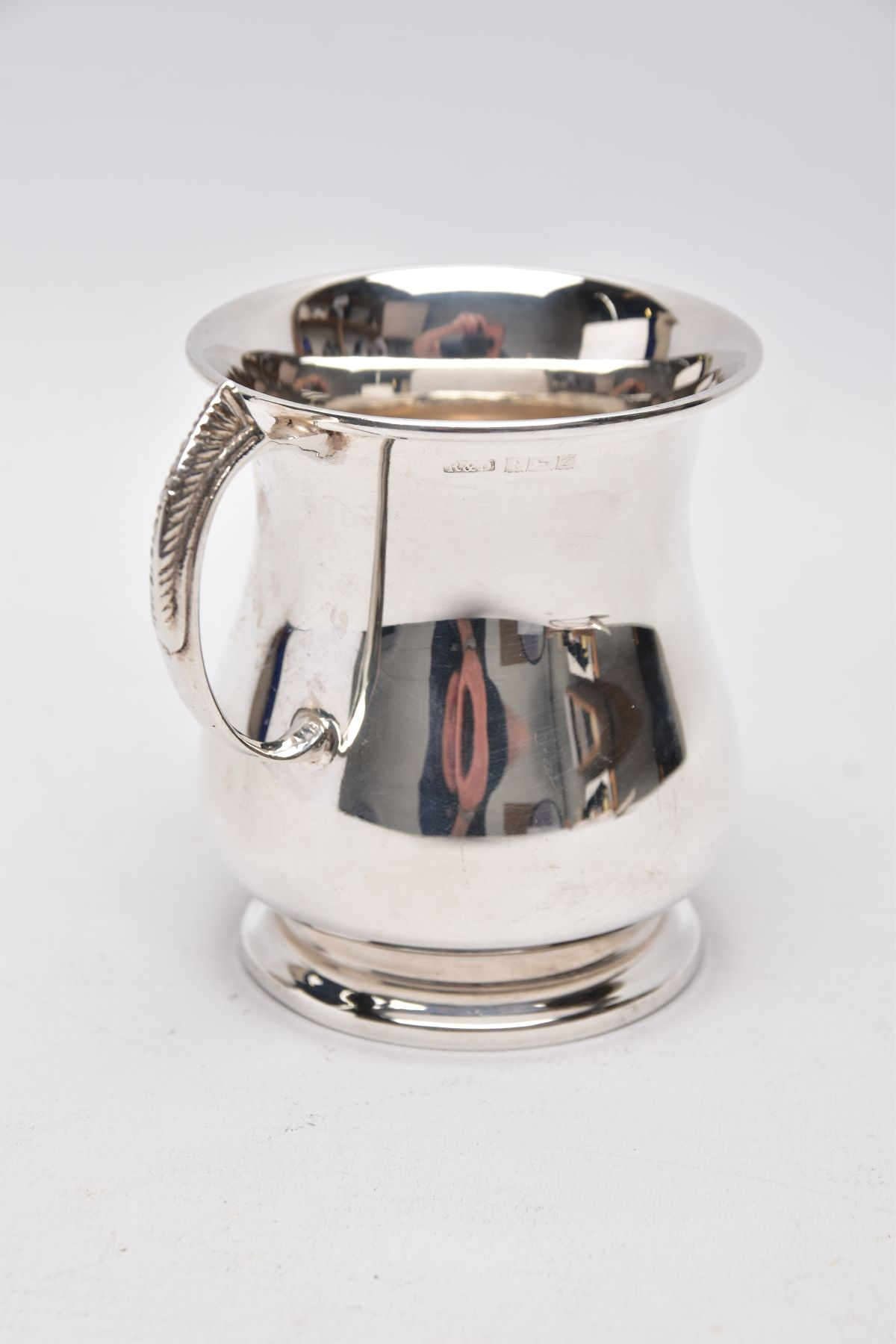 A SILVER TANKARD, bell shaped body with a feather detailed handle, hallmarked 'Roberts & Dore'