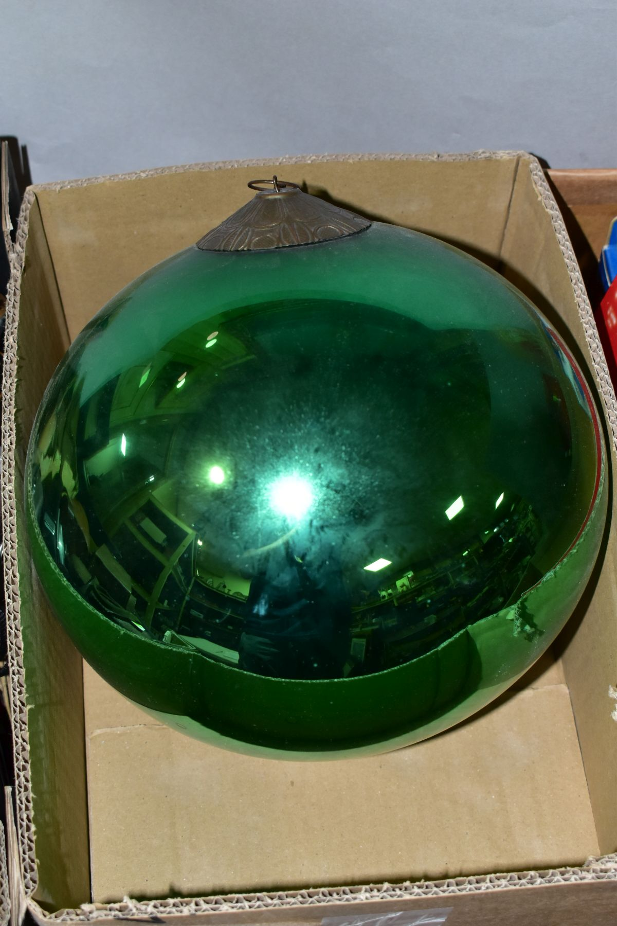 A LATE 19TH/EARLY 20TH CENTURY METALLIC GREEN GLASS WITCH'S BALL with metal mount and short length