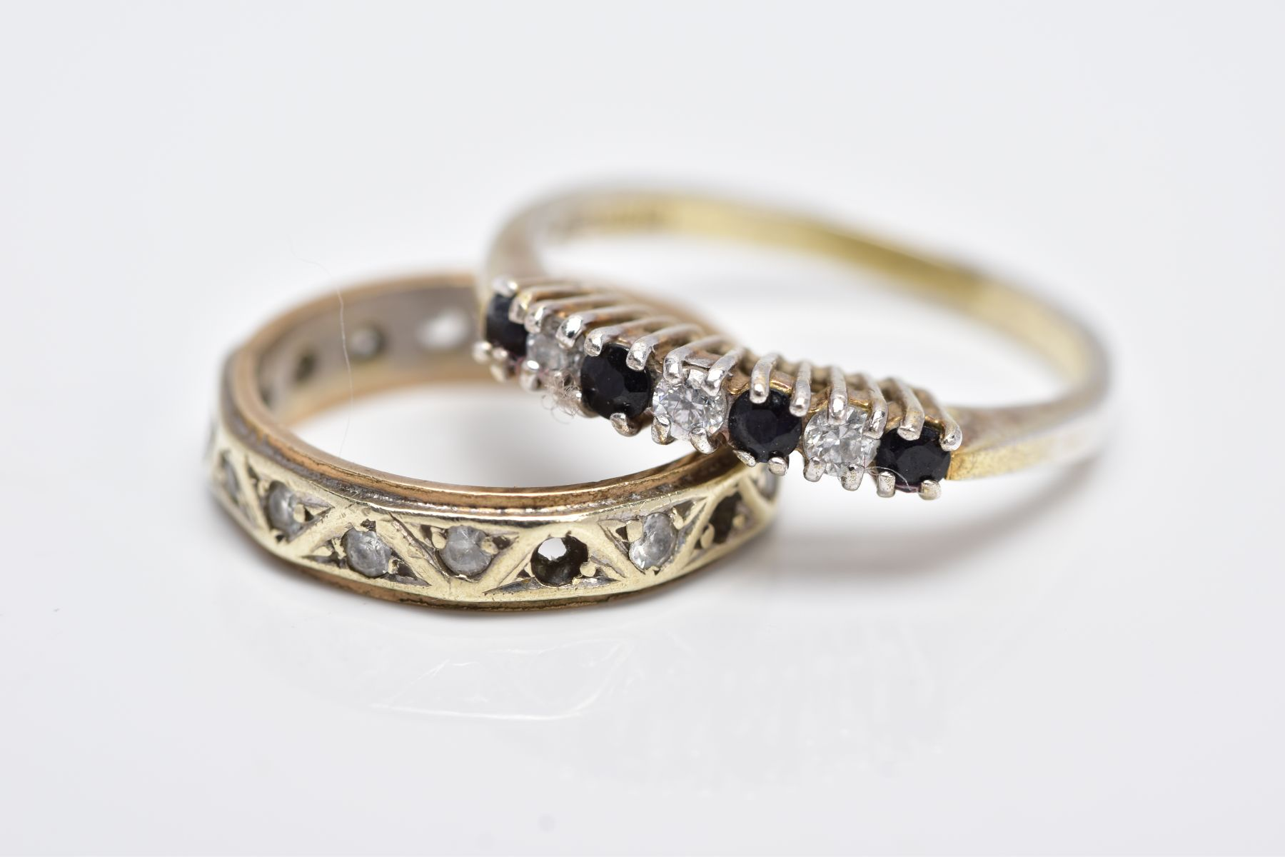 A YELLOW METAL FULL ETERNITY RING AND A SILVER GEM SET RING, the full eternity ring set with