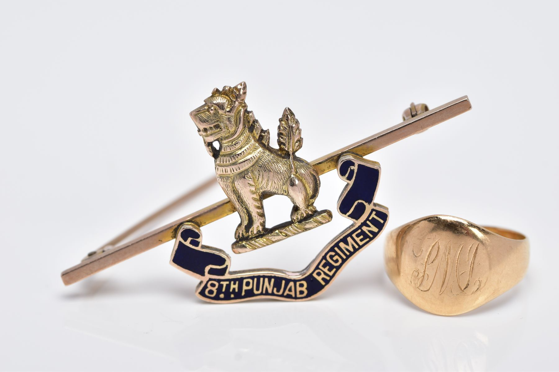 AN 18CT GOLD SIGNET RING AND A YELLOW METAL REGIMENT BADGE, oval signet ring with an engraved