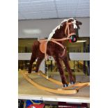 A MODERN WOODEN ROCKING HORSE, covered in brown plush with string tail and mane, painted mouth, nose