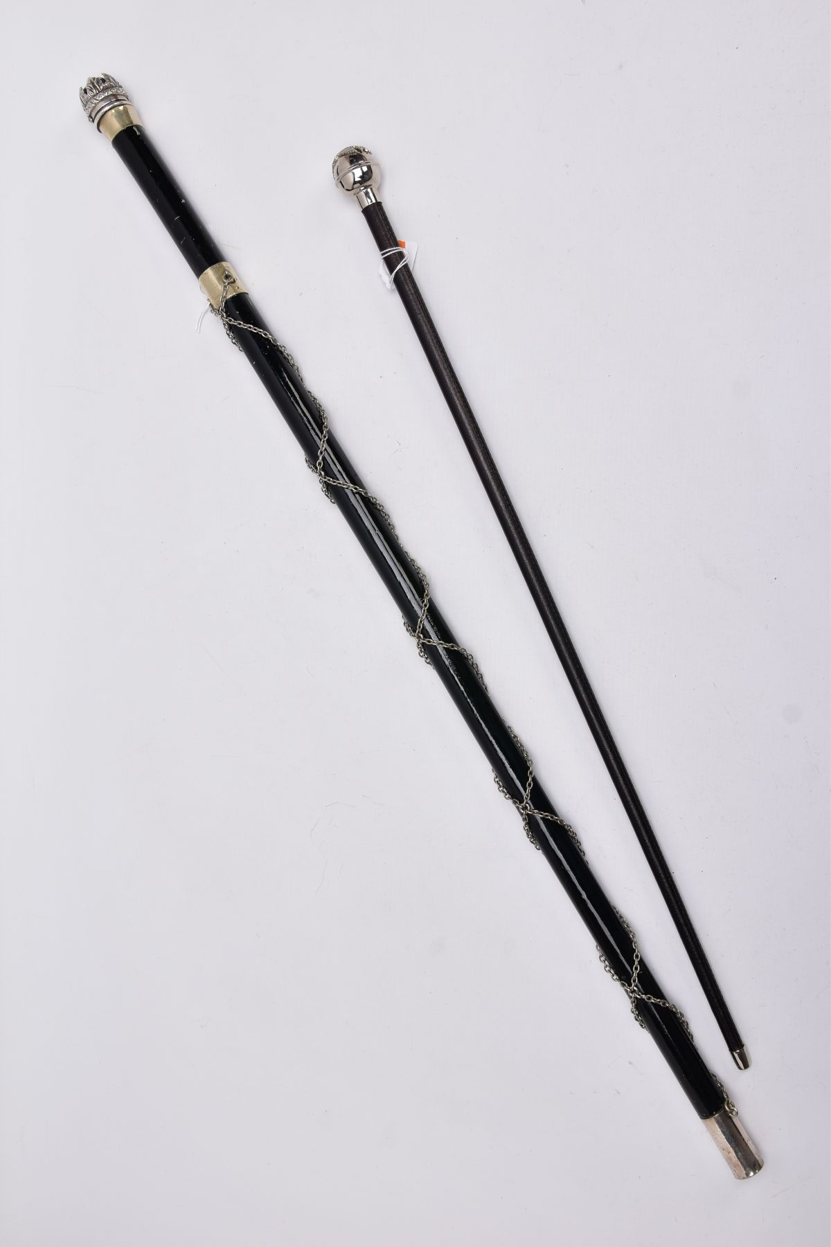 TWO MILITARY RELATED SWAGGER STYLE STICKS, to include a white metal sphere topped with white metal