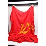 A LARGE RED/GOLD COLOURED RUSSIAN (CCCP) FLAG, approximately six feet x eight feet, corded and bound