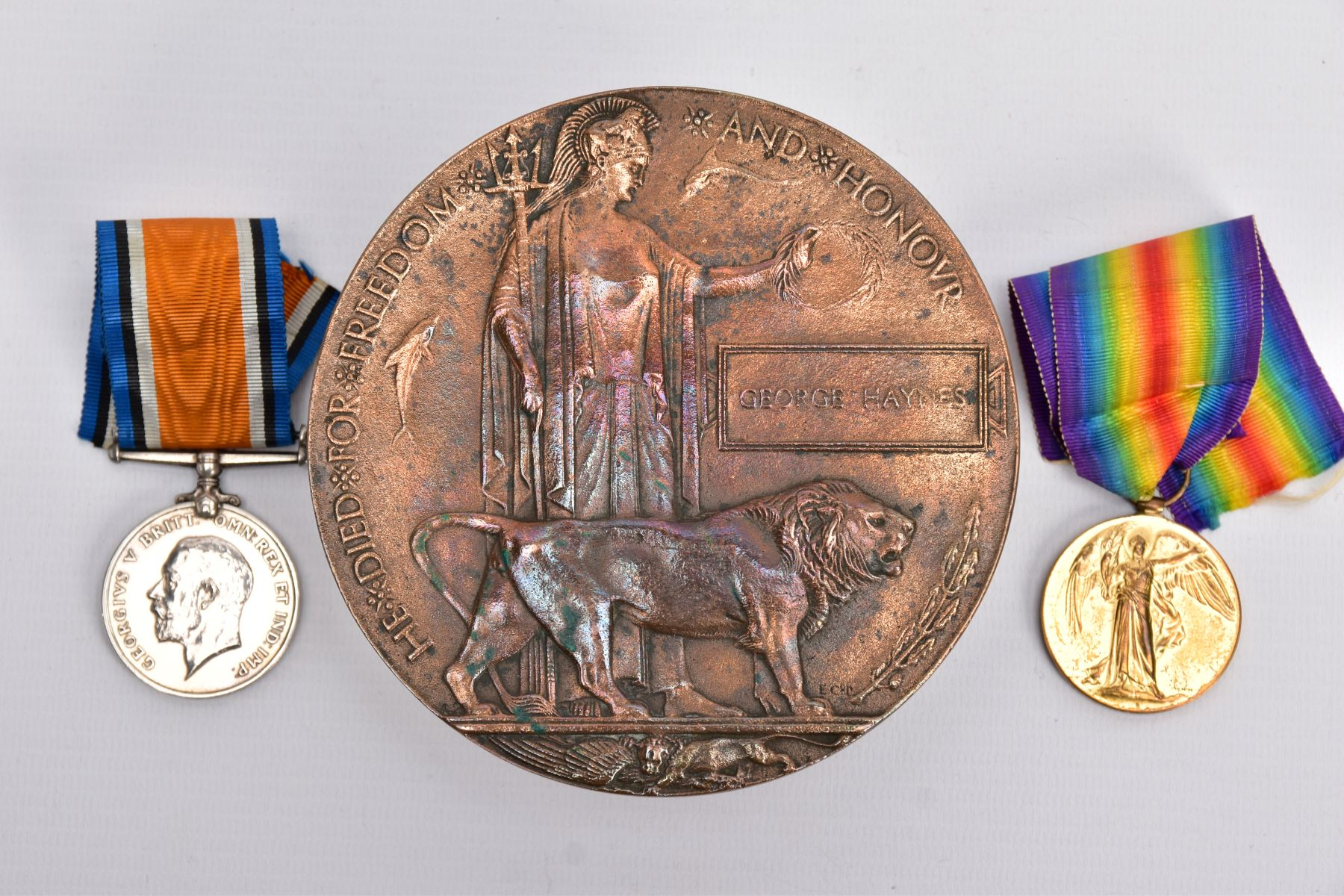 A WWI MEMORIAL DEATH PLAQUE named George Haynes, together with a British War and Victory medal named