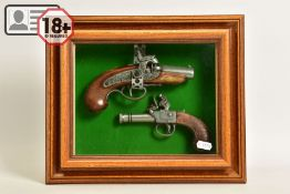 A NEATLY FRAMED DISPLAY CASE containing a white metal replica of a percussion American derringer and