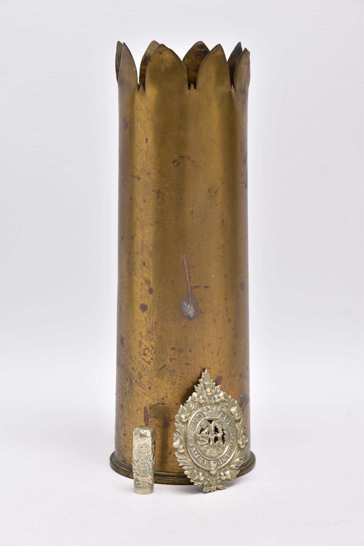 A WWI ERA 18LB SHELL CASE which has a cut out petal style around rim, together with silver