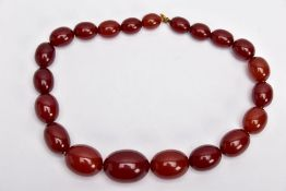 A CHERRY AMBER GRADUATED BEAD NECKLACE, the largest measuring approximately 31.7mm x 23.3mm, the