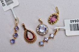 A 9CT GOLD GARNET PENDANT AND FOUR OTHER YELLOW METAL PENDANTS, the first set with a pear cut