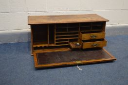 AN OAK TABLE TOP SECRETAIRE CABINET, with a fall front door with internal Burgandy leather inlay