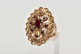 A 9CT GOLD GARNET DRESS RING, of a large openwork marquise shape, set with circular cut garnets,