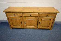 A MODERN SOLID GOLDEN OAK SIDEBOARD, three drawers above three cupboard doors, width 201cm x depth